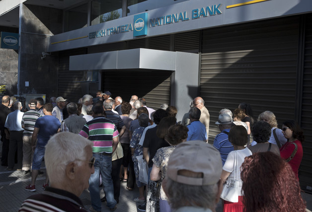Ciudadanos de Grecia se agolpan a las puertas de un banco cerrado por el corralito, este lunes en Atenas.