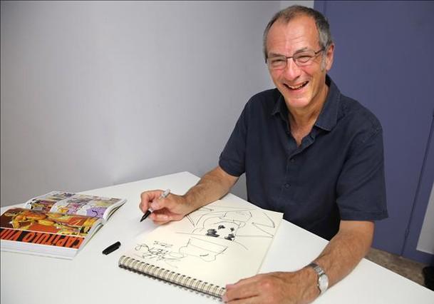 Dave Gibbons, en Barcelona, tras dibujar el personaje de Rorscharch, con un ejemplar de 'Watchmen' al lado.