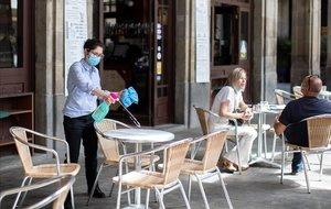 Desinfección de mesas en una terraza en la plaza Reial.