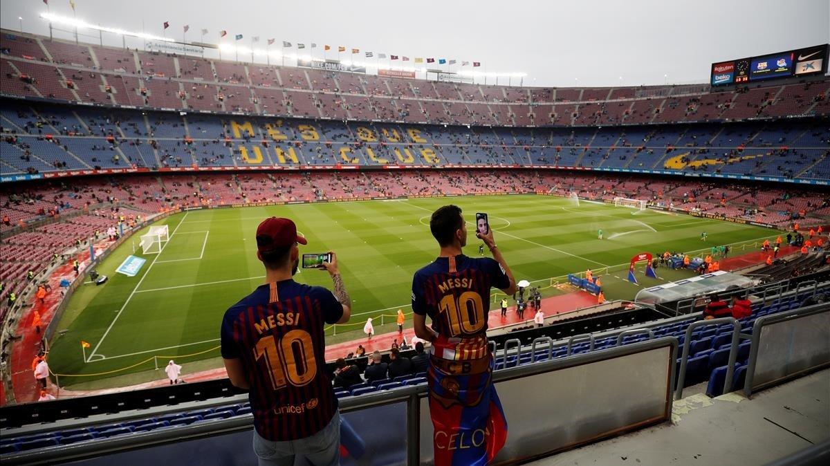 Dos aficionados fotografían el interior del Camp Nou