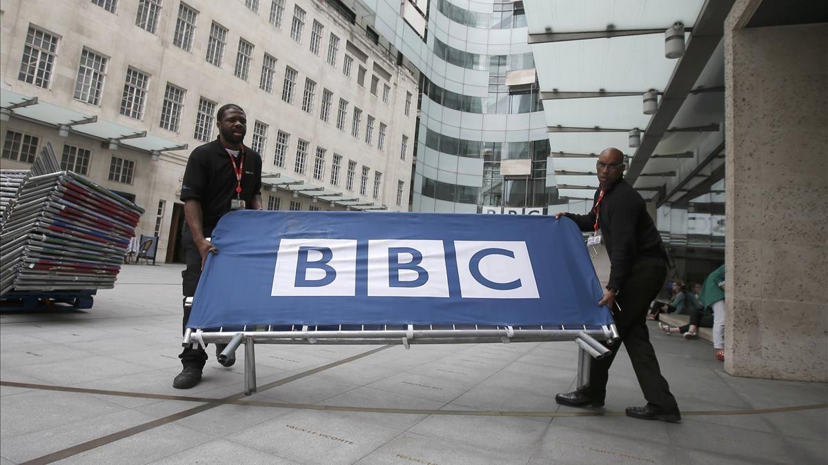 Dos empleados de la BBC sitúan barreras cerca de la entrada principal del cuartel general de la BBC en Portland Place, en Londres, el 16 de julio del 2015.