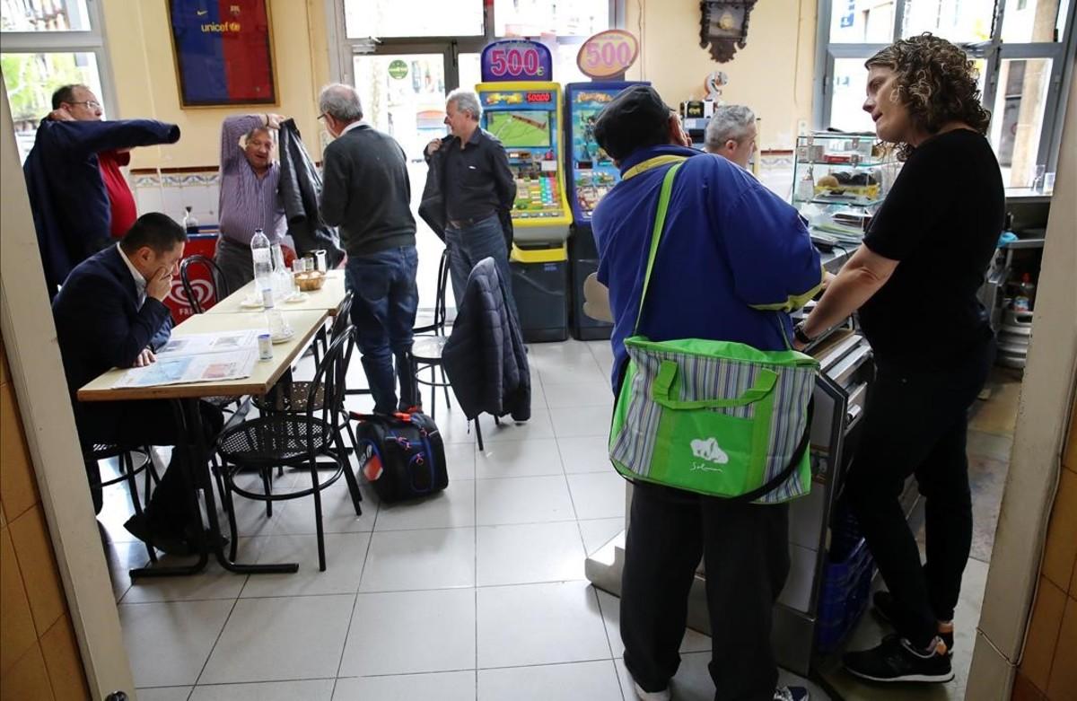 Laura Albéniz, a la derecha, charla con un cliente en el Bar Gelida del Eixample, donde una parte de la clientela son personas mayores del barrio que hace años que acuden.