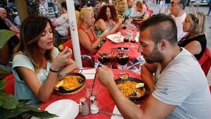 Turistas comiendo y bebiendo en un local de la Rambla de Barcelona.