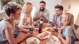 Un grupo de amigos conversa alrededor de la mesa, durante una comida.