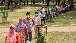 Un grupo de personas hacen cola para recibir comida gratis del Gobierno, este martes en Nueva Deli.
