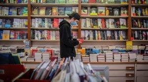 Un joven con mascarilla hojea un libro en una papelería-librería de Barcelona.
