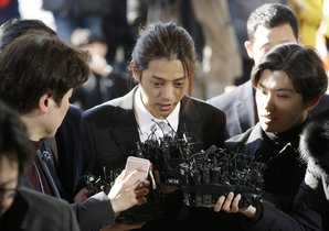 FILE - In this March 14, 2019, file photo, K-pop singer Jung Joon-young, center, speaks upon his arrival at the Seoul Metropolitan Police Agency in Seoul, South Korea. A South Korean court has found two K-pop stars guilty of illicit sexual relations with a woman who was unable to resist and sentenced them to up to six years in prison. The Seoul Central District Court says singer-songwriter Jung received a six-year prison term. (AP Photo/Ahn Young-joon, File)