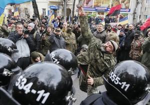 Manifestantes lanzan piedras a un banco ruso en un acto de protesta en Kiev.