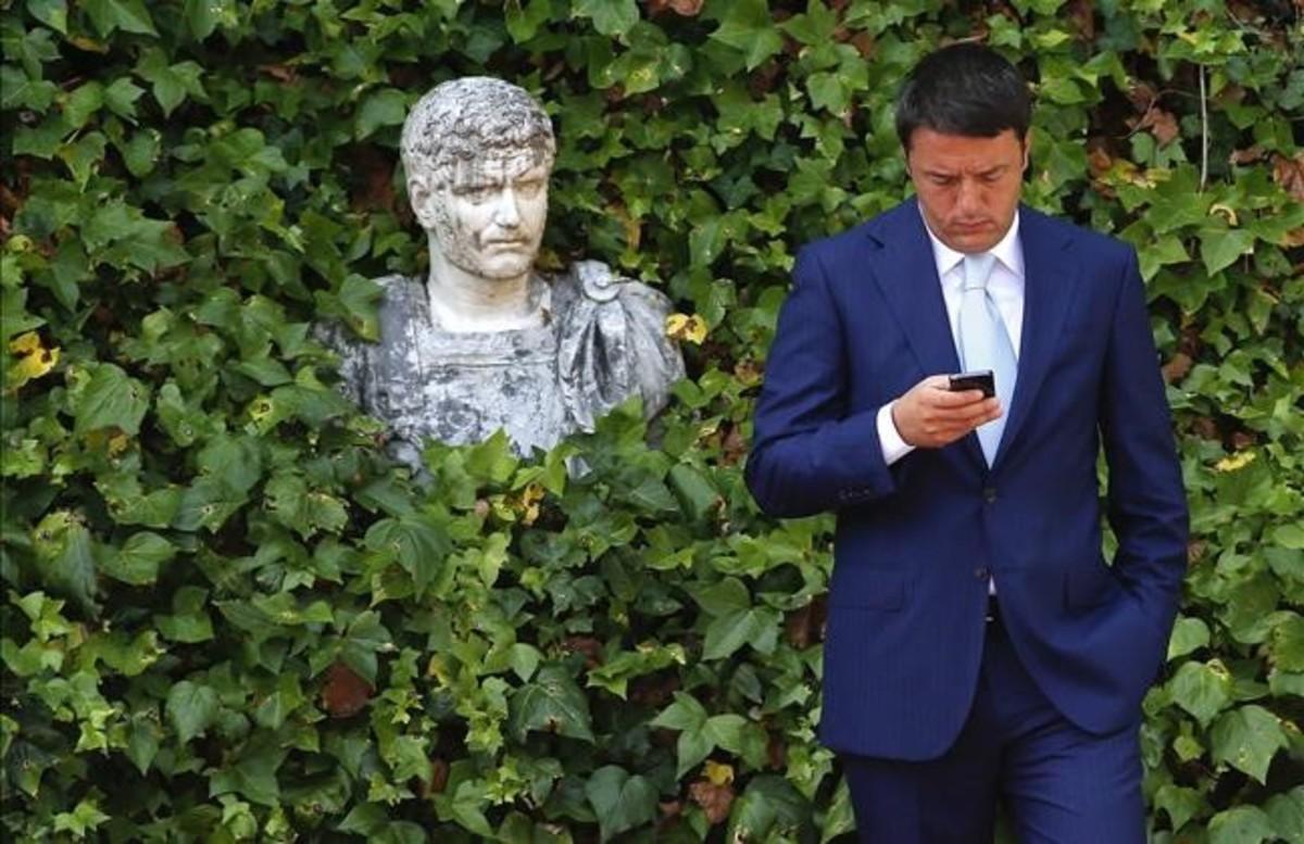 Matteo Renzi mira al móvil mientras espera la llegada del presidente de la Comisión Europea, en verano del 2014, en Roma.