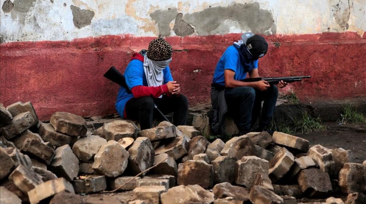 Miembros de las fuerzas gubernamentales sentados sobre lo que queda de las barricadas destruidas en el barrio de Monimbo