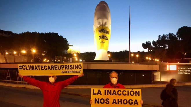Greenpeace posa una mascareta gegant a una estàtua de la plaça de Colón de Madrid