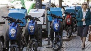 Motos de reparto aparcadas en una acera de València.