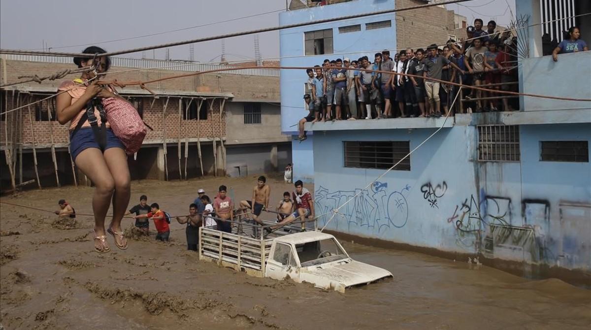 Una mujer es evacuada en una calle inundada por las lluvias enLima.