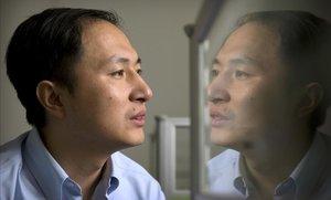 El doctor He Jiankui, reflejado en un panel mientras trabaja con el ordenador.
