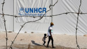 Una mujer y un niño camino tras la reja del nuevo campo de refugiados provisional de Lesbos, en Grecia.