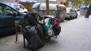 Un sintecho duerme en un banco de la calle de Vilà i Vilà, en el Poble Sec.