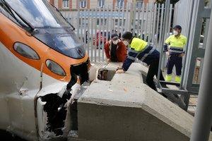 Técnicos de Renfe observan el punto del impacto del tren accidentado en Mataró con el final de vía.