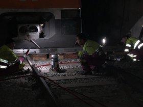 Técnicos de Renfe trabajan para encarrilar el tren accidentado en el túnel de Toses.
