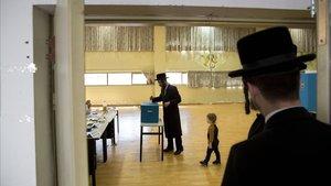 Un joven ultraortodoxo vota hoy en un colegio electoral de Bnei Brak.