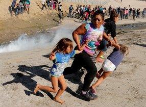 Una mujer hondureña huye con sus hijas de los gases lacrimógenos, este domingo en Tijuana.