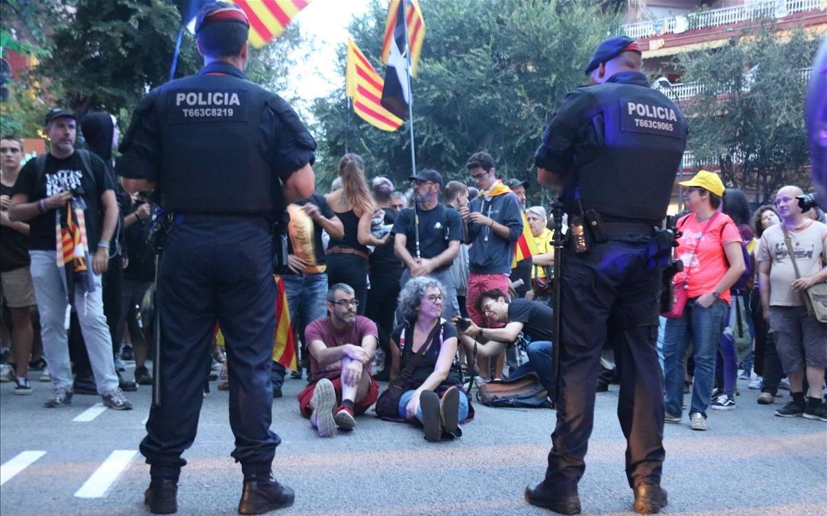 Dos agents dels Mossos d'Esquadra, davant d'un grup de persones d'ideologia independentista concentrades a la caserna de la Guàrdia Civil de Travessera de Gràcia a Barcelona, el 20 de setembre passat.
