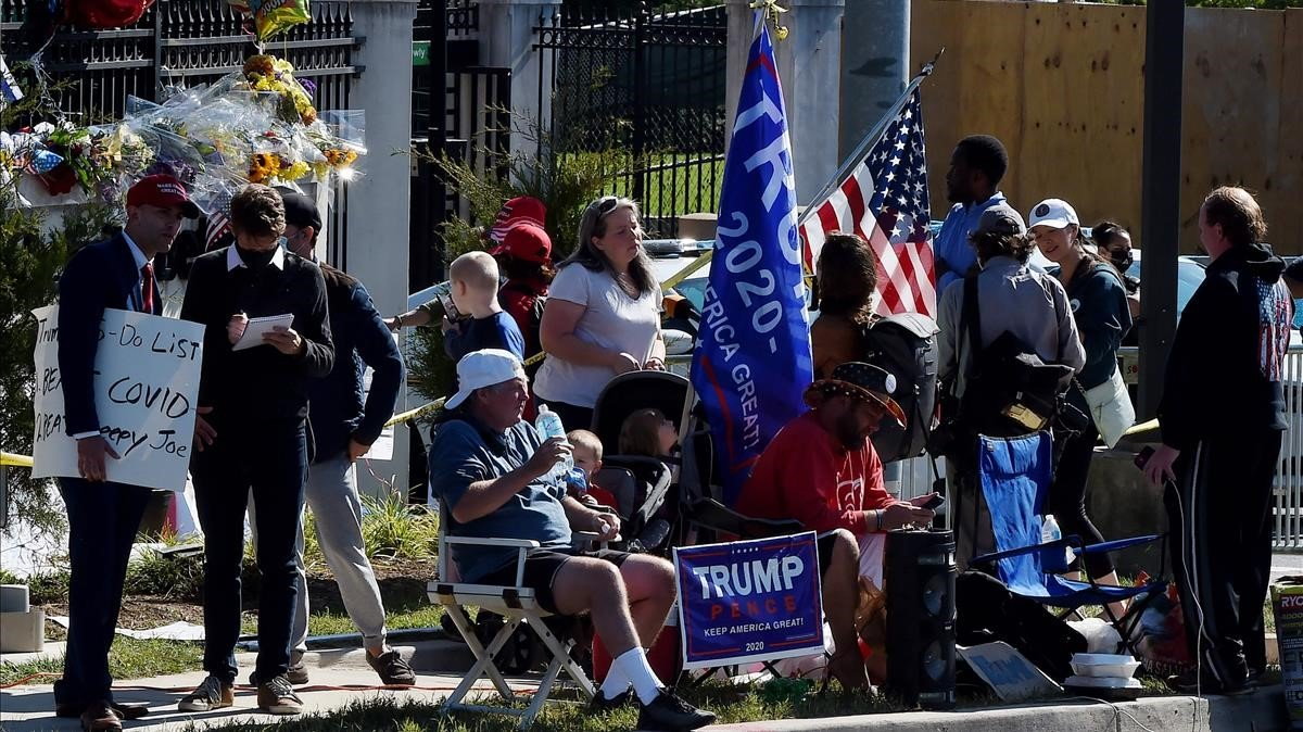 Varios de los seguidores de Trump que montan guardia a las puertas del hospital, este lunes.