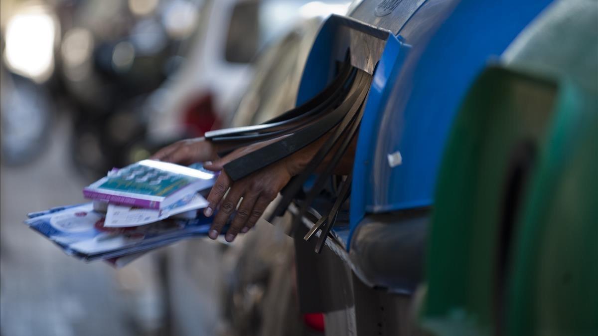 Una mano anónima arroja desde el interior de un contenedor para papel unas revistas.