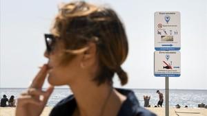 Una joven da la última calada a su cigarrillo antes de entrar en el espacio delimitado como libre de humo en la playa de El Masnou.