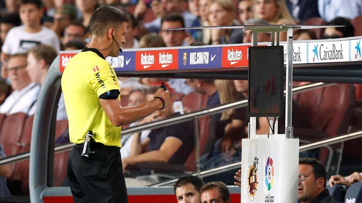 Gil Manzano chequea la jugada que condujo a la expulsión de Lenglet, en el Barça-Girona de Liga.