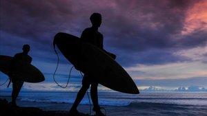 Jóvenes indonesios caminan con sus tablas de surf en una playa de Aceh, en la isla de Sumatra.
