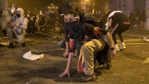 Una joven, con gafas de protección, atenta a los movimientos policiales, durante los disturbios del 17 de octubre.