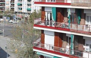 Unos vecinos toman el sol en el balcón.