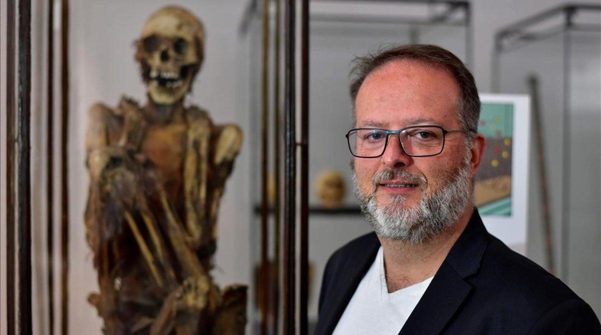 El arqueólogo Serge Lemaître posa ante la momia inca que supuestamente inspiró a Hergé para el personaje Rascar Capac, este martes en el Museo de Arte e Historia de Bruselas.