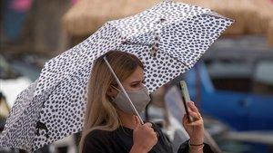 Una turista protegiéndose de la lluvia mientras se hace un selfie.