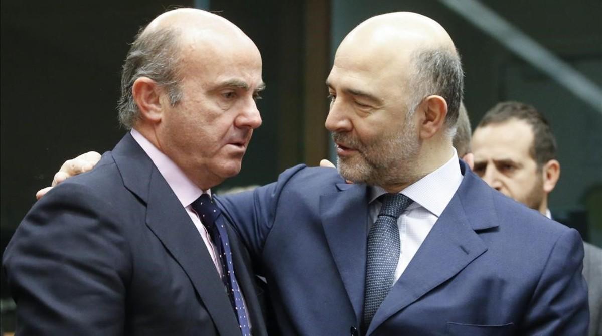El ministro espanol de Economia, Luis de Guindos, conversa con el comisario europeo de Asuntos Economicos, Pierre Moscovici.