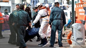 Miembros de Salvamento Maritimo y Guardia Civil trasladan al puerto de Almeria los cadaveres de tres varones que viajaban en una de las dos pateras rescatadas