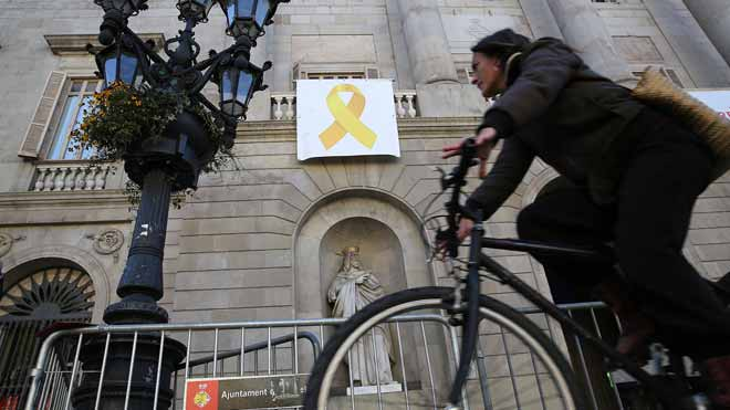 Un grup de persones despenja el llaç groc de l'Ajuntament de Barcelona i ho intenta a la Generalitat