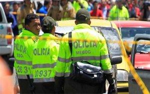 Policías de Colombia resguardan la zona de un asesinato.