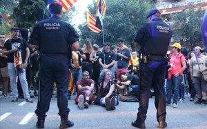 Dos mossos, ante un grupo de manifestantes que organizó una sentada ante la sede de la Guardia Civil en la Travessera de Gràcia de Barcelona, el pasado día 20.