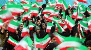 Estudiantes ondean banderas iranís durante la ceremonia de conmemoración de la revolución.