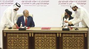 Firma del acuerdo de paz entre el enviado estadounidense, Zalmay Khalilz,(izquierda) y el mulá Abdul Ghani Baradar.