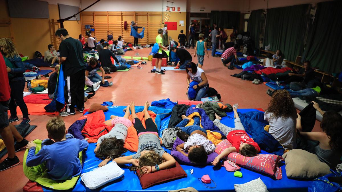 La gente que ha dormidoen el Colegio La Llacuna de Poblenou se despierta y se disponepara habilitar el colegio electoral.