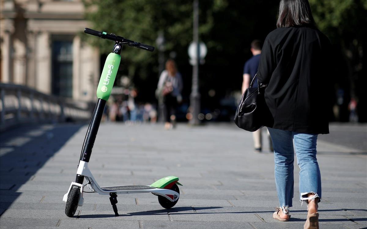 Una mujer con un patinete eléctrico en París.