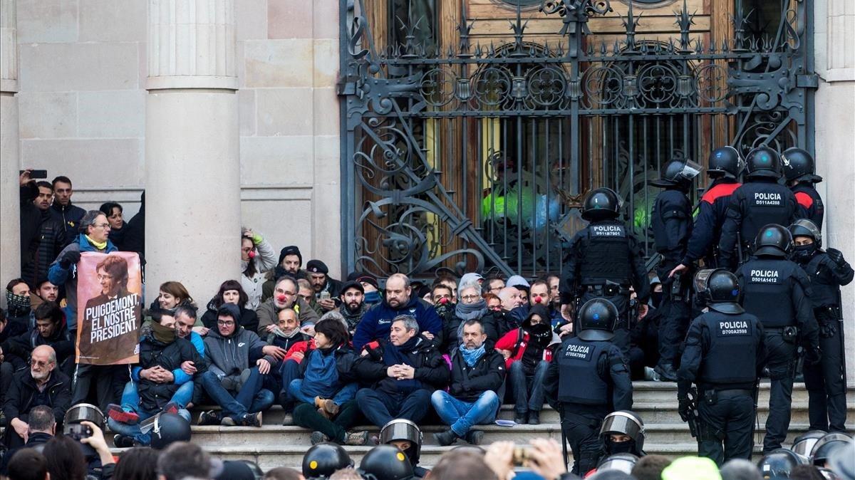 Agentes de los Mossos d'Esquadra desalojan a las decenas de personas que se han encadenado a las puertas del Tribunal de Justicia de Catalunyaconvocados por los Comités de Defensa de la República (CDR)