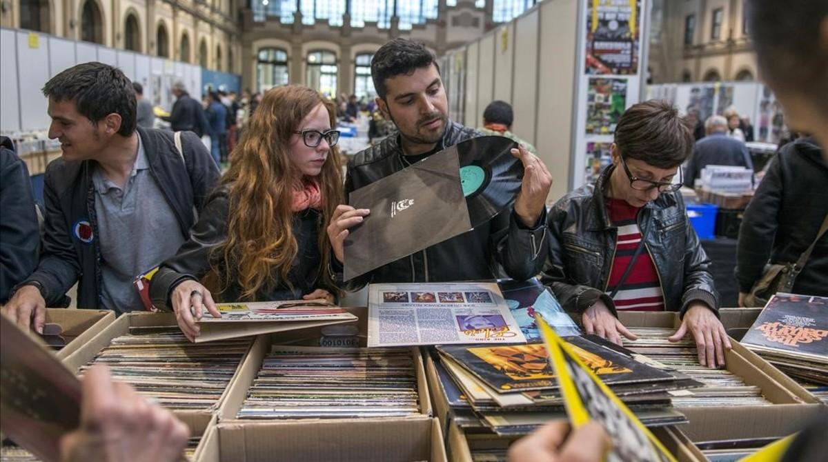 Unos jóvenes observan un disco de vinilo en la21ª Fira del Disc Internacional de Barcelona, este domingo.