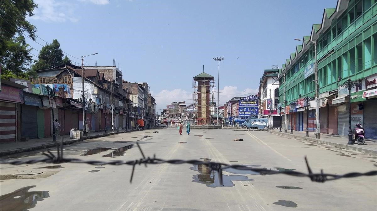 Mujeres caminan por una calle desierta en Srinagar, en la Cachemira india, este jueves.