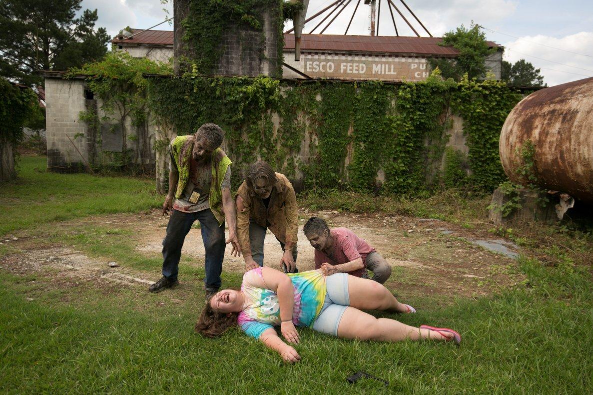 Otra visitante del parque, Skylar Powers, tendida en el suelo, muerta de risa, rodeada de zombis.