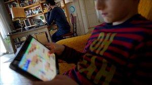 Un padre teletrabaja mientras su hijo juga con el iPad, hoy en Madrid.