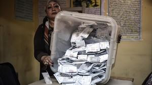 Una miembrode una mesa electoral muestralas papeletas depositadas en una urna en El Cairo.