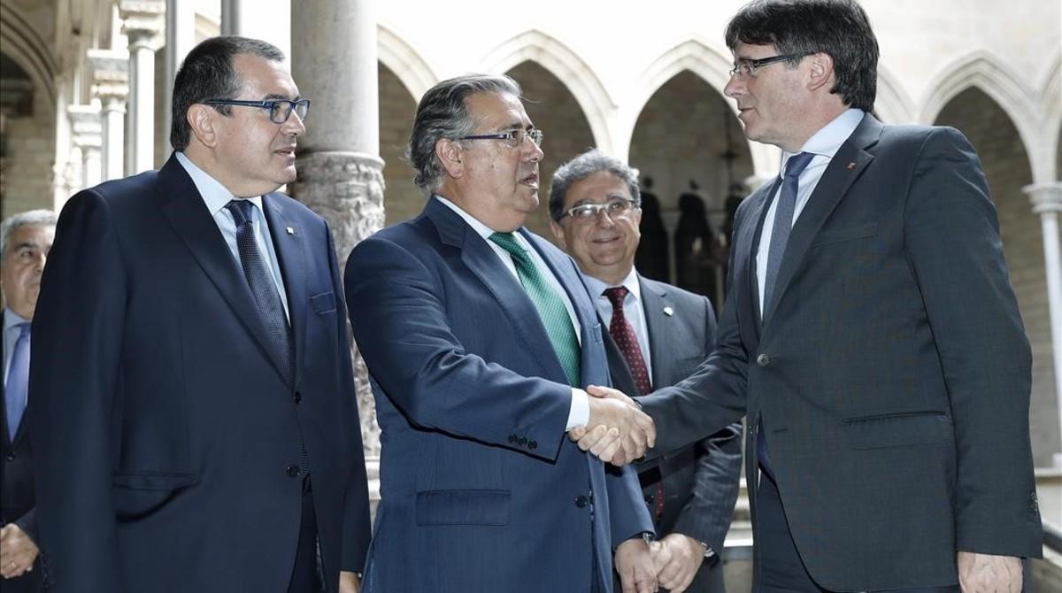 El presidente de la Generalitat, Carles Puigdemont, saluda al ministro del Interior, Juan Ignacio Zoido, ante el 'conseller' de Interior, Jordi Jané, el 10 de julio, antes del comienzo de la reunión de la Junta de Seguridad.